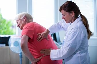 Weiblicher Doktor, der einen Patienten überprüft