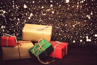 Weihnachten Hintergrund - Weihnachtsgeschenk Geschenk-Box und Schnee auf alten hölzernen Hintergrund. Vintager Farbton