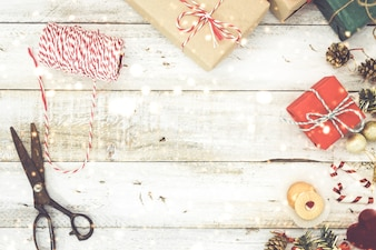 Weihnachten präsentiert Verpackung und Schnee über Holztisch Hintergrund mit Kopie Raum. Geschenkverpackung für Weihnachten und Neujahr. Handgefertigt