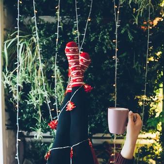 Weiße helle Girlande um die Beine in roten Socken