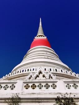 Weiße Pagode mit eingewickelten roten Kleidern im buddhistischen Tempel in Thailand