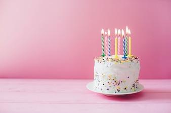Weißer Kuchen mit brennenden Kerzen