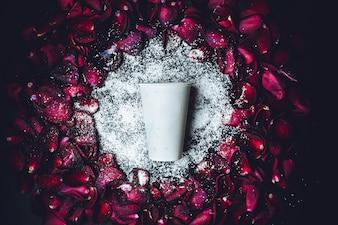 Weißer Pappbecher liegt im weißen Pulver im Kreis aus roten Rosenblättern