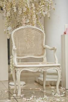 Weißer Stuhl steht auf weißen Blütenblättern draußen