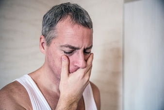 Zahnschmerzen. Frustrierter junger Mann, der seine Wange berührt und die Augen geschlossen hat. Leiden reifer Mann mit Zahnproblemen. Schmerzlicher Ausdruck