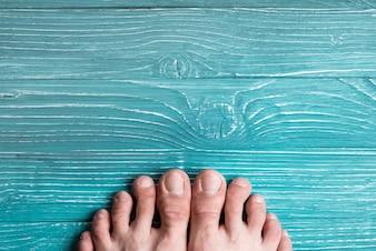 Zehen auf einem Hintergrund der blauen Brett