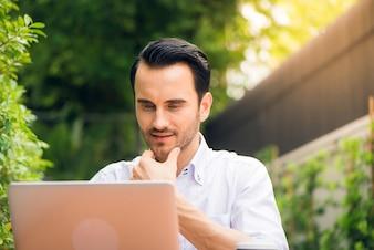 Zufriedene Geschäftsmann arbeitet am Laptop mit Internet Wireless