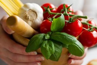 Zutaten zum Kochen von Nudeln. Tomaten, frischen Basilikum, Knoblauch, Spaghetti. Koch hält frische Zutaten zum Kochen. Nahansicht.