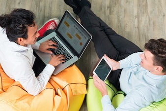 Zwei Business-Männer arbeiten auf Tablet und Laptop