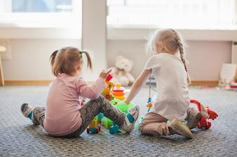 Zwei kleine Mädchen sitzen auf dem Boden spielen