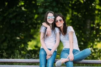Zwei Mädchen sitzen draußen umarmen lächelnd