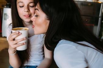 Zwei Mädchen sitzen mit Tasse Kaffee