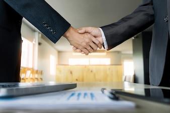 Zwei zuversichtlich Geschäftsmann Händeschütteln während einer Sitzung im Büro, Erfolg, Handel, Gruß und Partner-Konzept