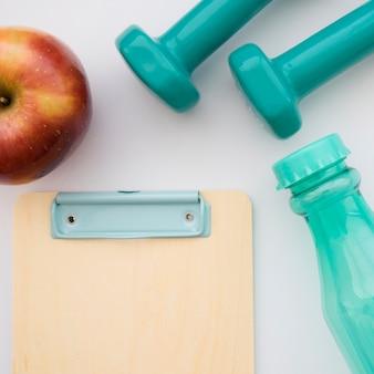 Zwischenablage, Apfel, Flasche und Hanteln close up