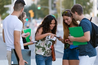 A group of students having fun with smartphones after class.
