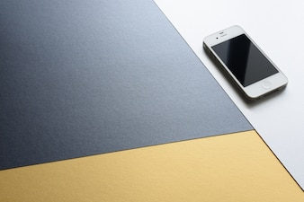 A mobile phone isolated on three colors modern design background. black, white and yellow color.o
