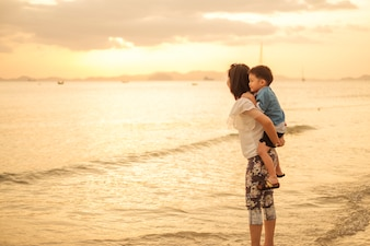 A mother and son in outdoors at sunset with copy space