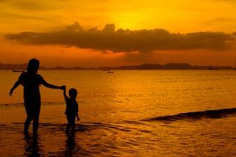 コピースペースのある日没の屋外での母と息子