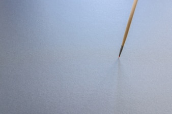 A thin tiped paint brush standing vertical, isolated on grey background.
