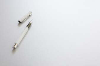 A white pen isolated on white writing paper, background.