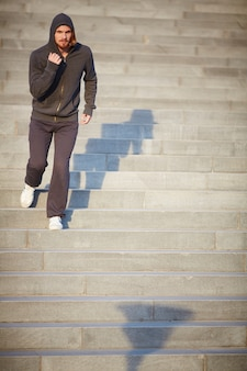 Active man running down city stairs
