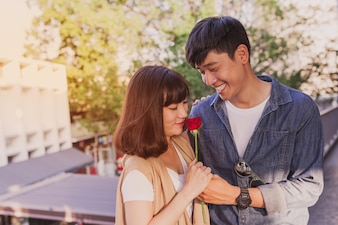 Adorable couple with a rose in hands