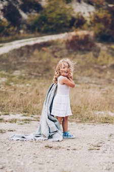 Adorable girl stay covered with  blanket in park