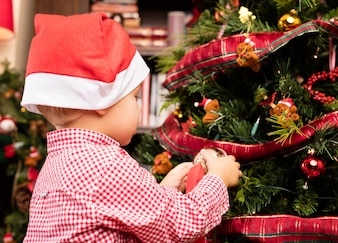 Adorable kid decorating a tree on christmas