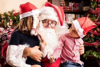Adorable kids sitting on a santa legs on christmas
