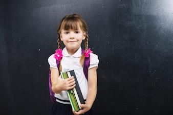 Adorable schoolgirl with books