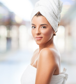 Adorable woman smiling at camera in towel