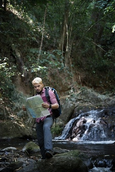Adventure man observing map on a mountain path  to find the the right way.