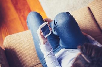 ソファーに座っている間に電話を読んでいる女の子の航空写真。ヴィンテージ調。