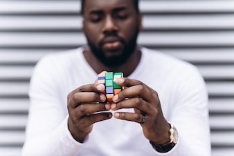 Afro American man wearing casual clothes in modern city collecting colored puzzle, close-up photo