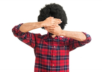 Afro man covering his face