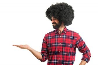 Afro man holding something