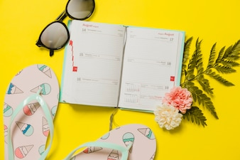 Agenda with flip-flops and sunglasses with reflections