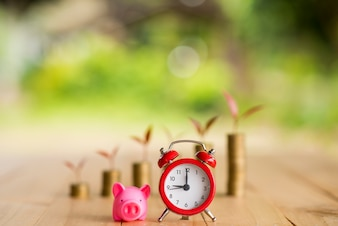 Alarm clock and piggy bank concept for saving time