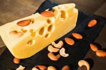 Almonds and peanuts on piece of tasty Swiss cheese