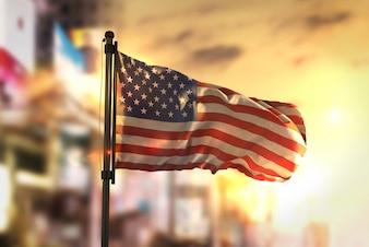日の出のバックライトで街を曇らせた背景に対するアメリカの旗