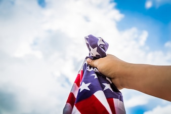 American flag held by a hand with clouds background