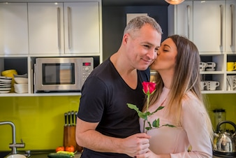 Amorous couple celebrating Valentine day at home in the kitchen. Romantic couple with rose while standing in kitchen