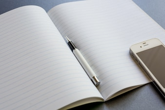 An opened notebook with a pen and mobile phone, on dark grey background, scene work or study.