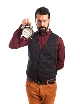Angry man wearing waistcoat holding vintage clock