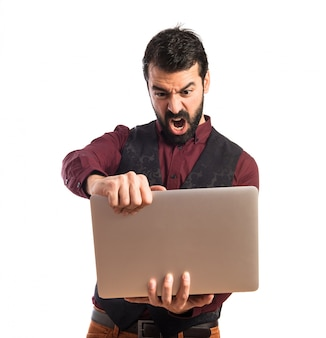 Angry man wearing waistcoat with laptop