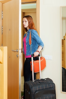 Angry woman leaves home with suitcase