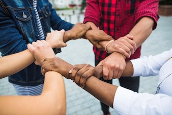Anonymous multiracial people stacking hands