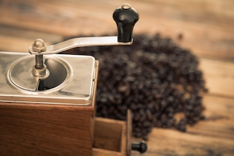 Antique coffee grinder with coffee beans behind