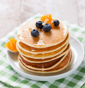 Appetizing pancakes with honey and marmalade