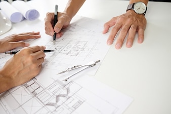 Architects engineer discussing at the table with blueprint - Closeup on hands and project print.